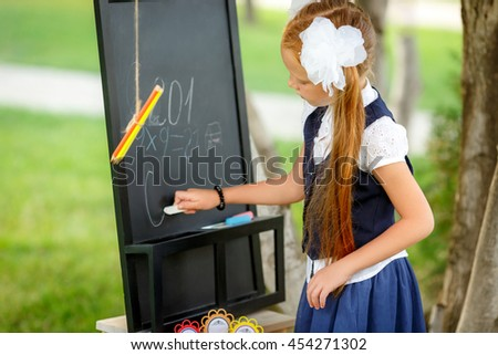 girl writing at the blackboard. first grader - stock photo
