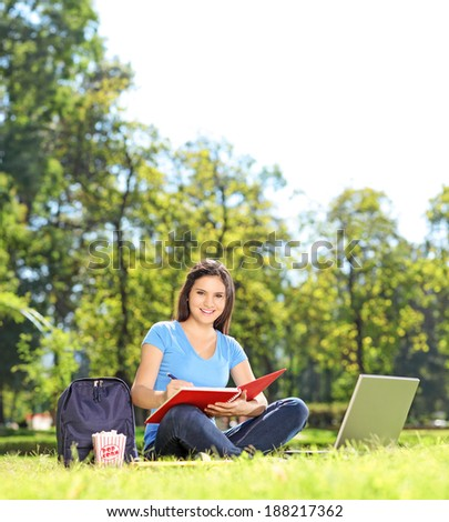 Girl writing in a notebook and looking at camera outdoors shot with tilt and shift lens - stock photo