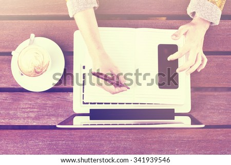 Girl writing in blank diary with cell phone and cup of coffee on wooden table - stock photo