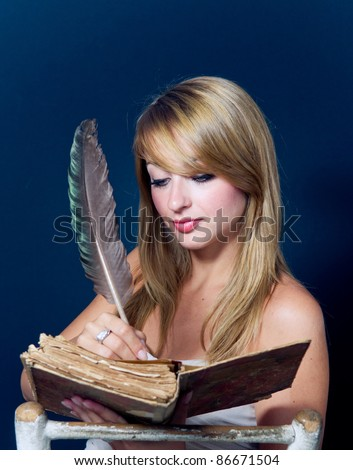 Girl writing in old book with quill pen. Dark blue background. - stock photo