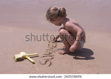 Girl writing in the sand on the beach - stock photo