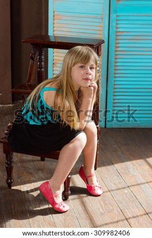 Girl 6 years old in a dress sits on a chair near wall - stock photo