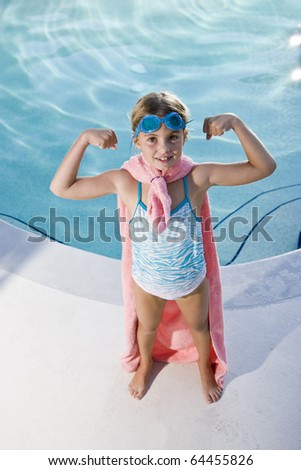 Girl, 7 years, playing by swimming pool in pretend superhero costume flexing muscles - stock photo