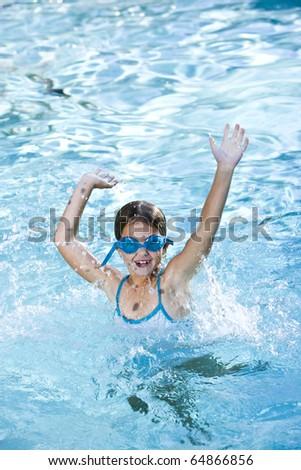 Girl, 7 years, wearing swim goggles, having fun splashing in pool - stock photo