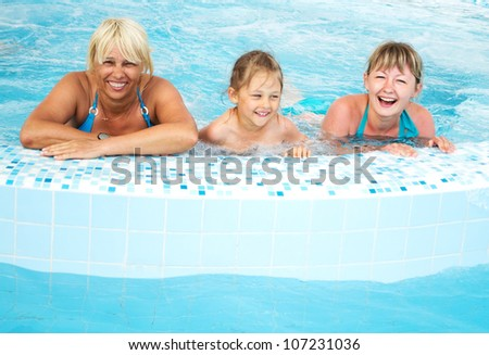 girl, young woman and middle-aged woman in a swimming pool with blue water - stock photo