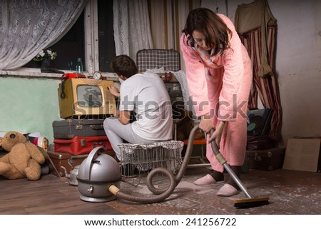 Girlfriend in Pink Robe Cleaning an Abandoned Room Using Vacuum While Boyfriend Busy Working with Old Unused Items at the Back. - stock photo