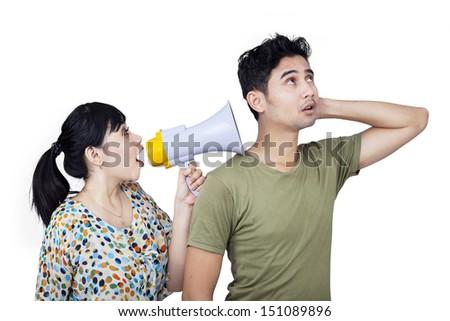 Girlfriend is shouting to her boyfriend using speaker on white background - stock photo