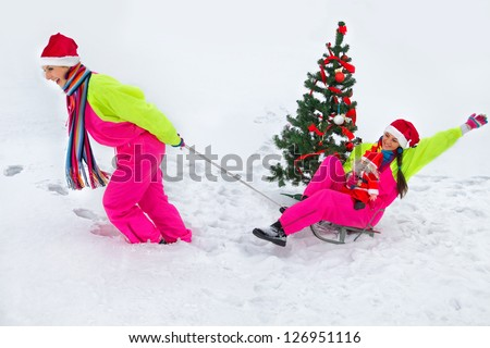 Girlfriend pulling Santa girl on a sled at snow - stock photo