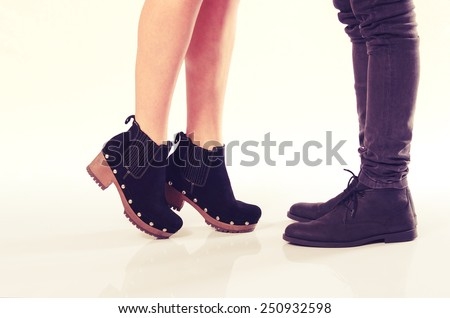 Girlfriend standing on her toes to reach and kiss her boyfriend