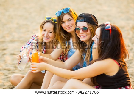 Girlfriends have fun and drink along the beach cocktails - stock photo