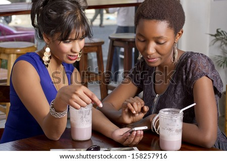 Girlfriends having drink at a coffee shop playing on a phone - stock photo
