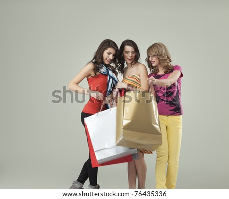 girlfriends looking inside shopping bags - stock photo