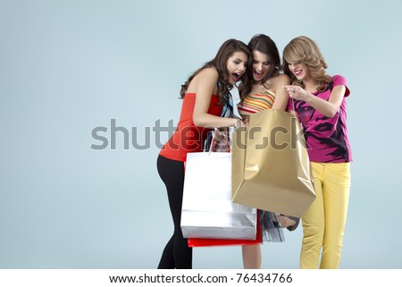 girlfriends looking inside shopping bags surprise - stock photo