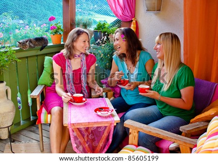 girlfriends sitting on a balcony and drinking coffee - stock photo