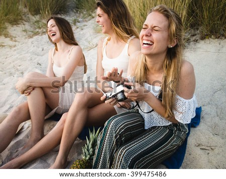 Girlfriends taking pictures at the beach party