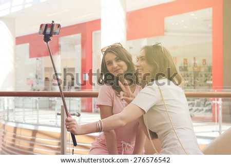 Girlfriends with smartphone in shopping mall - stock photo