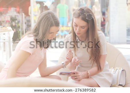 Girlfriends with smartphone in shopping mall. Toning foto - stock photo
