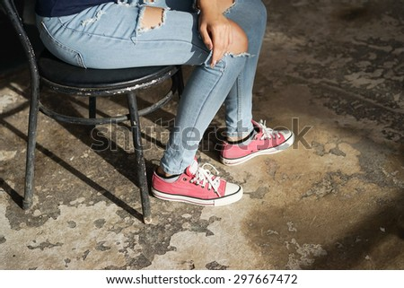Girlish legs in torn jeans