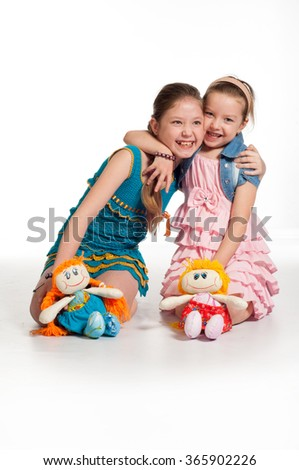 Girls and dolls. toddler girl with doll. Adorable toddlers happily hugging a doll. On a white background.  - stock photo
