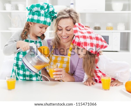 Girls and their mother making fresh orange juice in the kitchen - stock photo