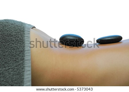 Girls back with hot stones. Part of hot stones massage. - stock photo
