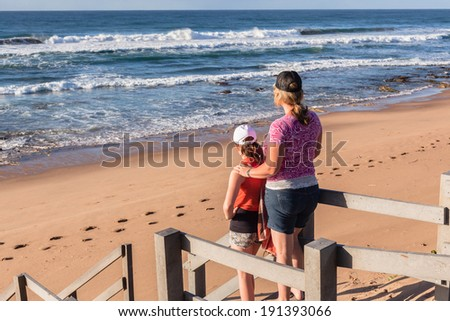 Girls Beach Ocean Stairs Mother daughter girls stand on walkway stairs  overlooking beach ocean waves and coastline early morning holidays - stock photo