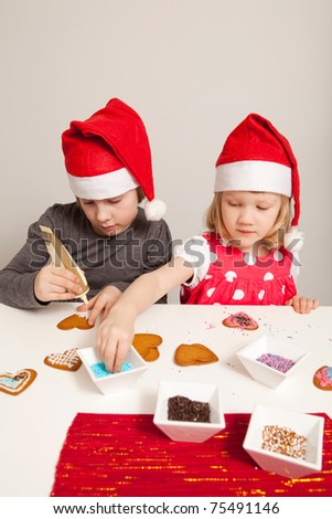 Girls decorating gingerbread cookies at Christmas. Studio shot.