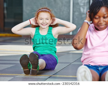 Girls doing sit-ups in physical education in elementary school - stock photo