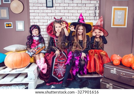 Girls, dressed up in Halloween costumes, show emotions of witches and vampires. - stock photo