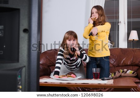 Girls eating sweets in front of tv - stock photo