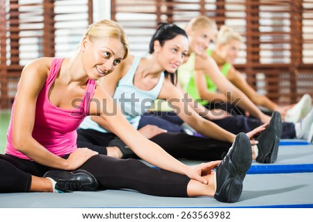 Girls exercising in gym, stretching body - stock photo