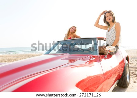 girls friends at beach in sports car convertible having fun - stock photo