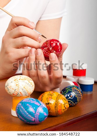 girls hand paint a group of Easter eggs - stock photo