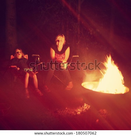 Girls having a campfire in night - Instagram effect - stock photo