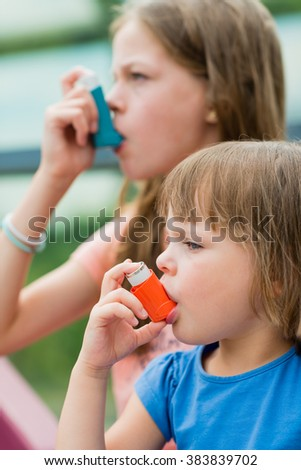 Girls having asthma using asthma inhaler for being healthy - shallow depth of field - stock photo