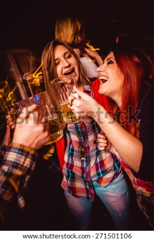 Girls having fun and drinking beer in night club