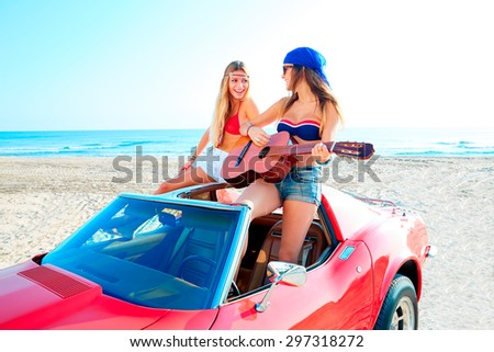 girls having fun playing guitar on th beach with a convertible car - stock photo