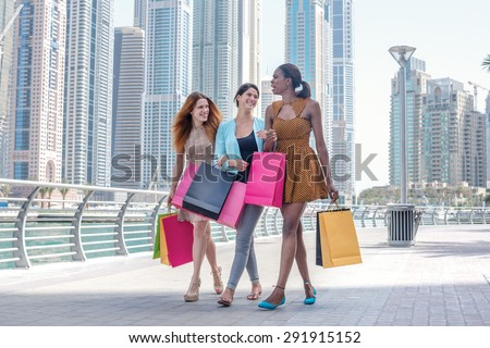 Girls having fun together shopping. Beautiful girl in dress holding shopping bags in their hands on the embankment among the skyscrapers while walking down the street with shopping bags - stock photo