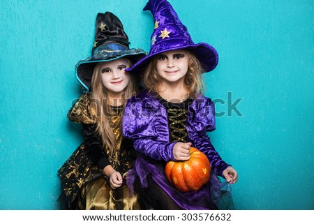 Girls in a suit of a witch. Halloween. Fairy. Tale. Studio portrait on blue background - stock photo