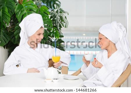 Girls in bathrobe drinking juice in spa salon - stock photo