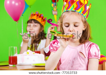 Girls in birthday crowns playing with party horns - stock photo