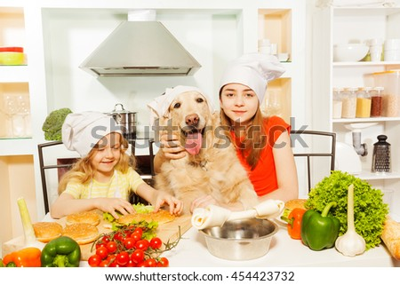 Girls in cook's hats making food with their pet - stock photo