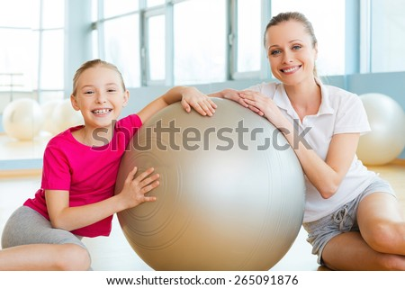 Girls in sports club. Cheerful mother and daughter leaning at the fitness ball and smiling while sitting on the floor in sports club  - stock photo