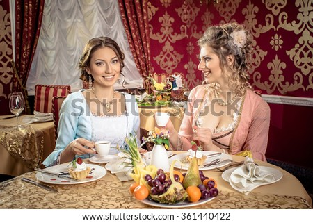 Girls in vintage dresses in the restaurant.  Retro Women Portrait. Romantic Beauty.Vintage Styled. Communication between two girls in the restaurant. - stock photo