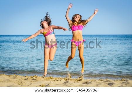 Girls jumping on tropical beach - stock photo