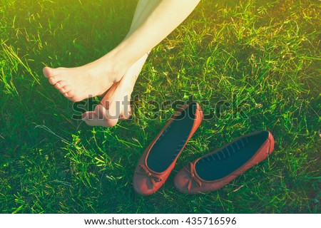 girls legs lying in grass barefoot without shoes - stock photo