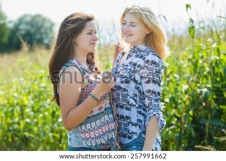 Girls listen to the music with one headphones for two - stock photo