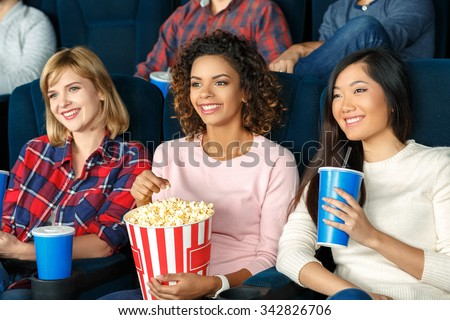 Girls night out. Beautiful young girls eating popcorn and watching a movie together  - stock photo