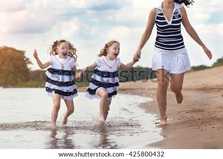 girls of the twin run on the river bank by a hand with mother with water splashes - stock photo