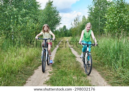 Girls on a bike ride on a country road